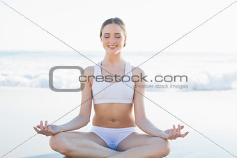 Peaceful smiling woman meditating on the beach