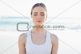 Calm young woman sitting on the beach