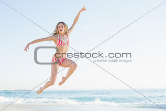 Attractive blonde woman jumping on the beach