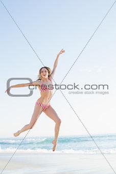 Beautiful blonde woman jumping on the beach