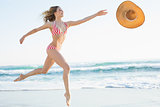 Elegant young woman jumping on beach