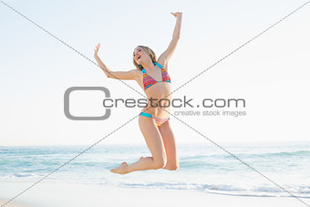 Beautiful blonde young woman jumping on beach