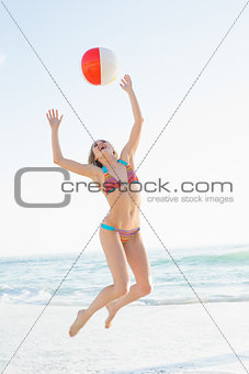 Beautiful young woman throwing a beach ball