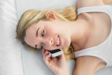 Beautiful woman phoning with her smartphone lying on her bed