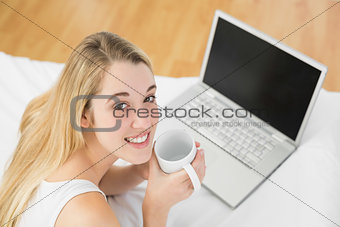 Calm young woman lying on her bed holding a cup