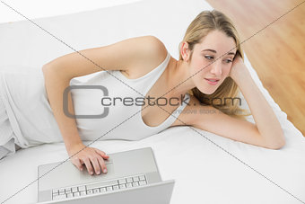 Thoughtful calm woman using her notebook lying on her bed