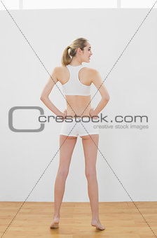 Attractive slender woman wearing sportswear posing standing in sports hall