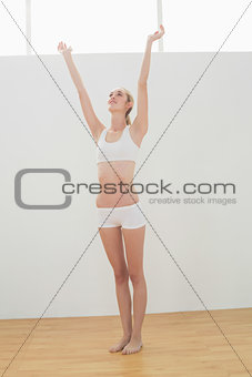 Slender fit woman stretching her body raising her arms