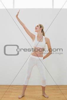 Attractive sporty woman doing yoga pose stretching her body