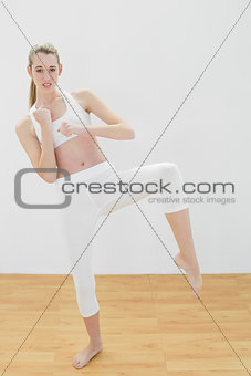 Beautiful toned woman practising martial arts in sports hall