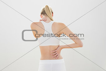 Slender sporty woman touching her injured nape