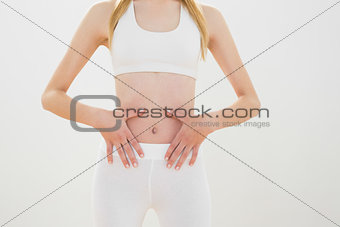 Slender sporty woman touching her belly