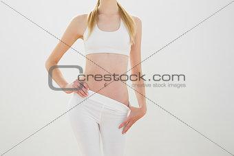 Slender blonde woman posing wearing sportswear with hand on hips
