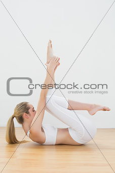 Attractive toned woman lying on floor stretching her leg