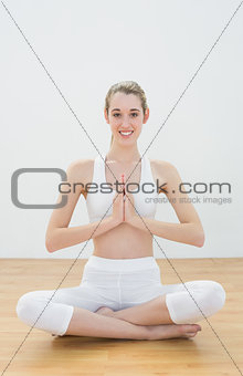 Calm toned woman sitting in lotus position in sports hall