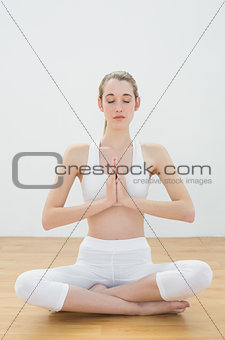 Fit peaceful woman sitting in lotus position on floor in sports hall