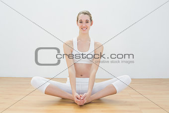 Attractive woman doing yoga pose sitting in lotus position in sports hall
