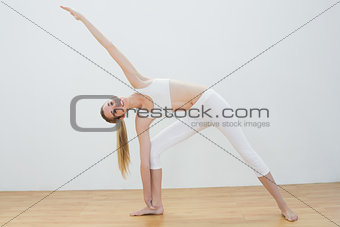 Fit young woman stretching her body in yoga pose