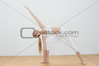 Attractive fit woman stretching her body standing in sports hall
