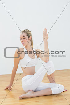 Concentrating ponytailed woman stretching her body sitting on floor