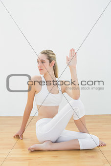 Focused toned woman stretching her body sitting on floor