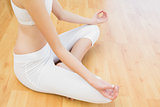 Young slender woman sitting on floor in lotus position