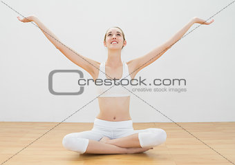 Peaceful young woman sitting in lotus position on floor