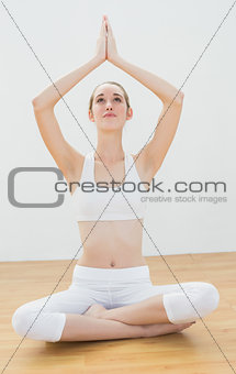 Attractive blonde woman sitting in lotus position raising her hands