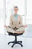 Focused chic businesswoman sitting in lotus position on her swivel chair