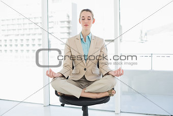 Attractive classy woman sitting in lotus position on her swivel chair