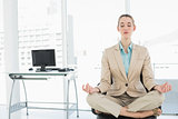 Concentrated calm businesswoman sitting in lotus position on her swivel chair