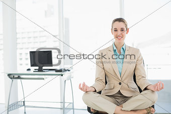 Beautiful calm woman sitting in lotus position on her swivel chair