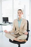 Lovely classy businesswoman meditating in lotus position on her swivel chair