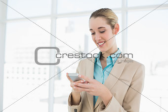 Attractive ponytailed businesswoman texting with her smartphone