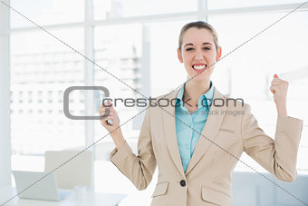 Attractive cheerful businesswoman holding her smartphone