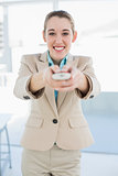 Attractive businesswoman holding a remote smiling cheerfully at camera