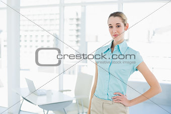 Attractive calm businesswoman posing in her office with hand on hip
