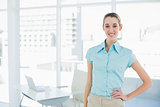 Cheerful attractive businesswoman posing with hand on hip