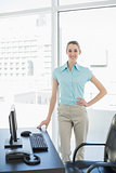 Happy beautiful businesswoman posing in her office with hand on hip