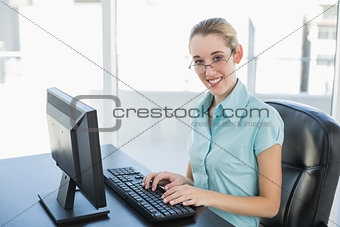 Beautiful calm businesswoman working on her computer smiling at camera