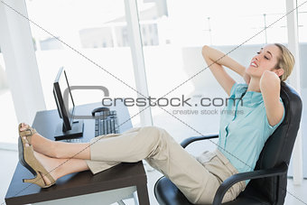 Classy young businesswoman relaxing sitting on her swivel chair
