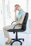 Exhausted classy businesswoman sitting on her swivel chair