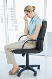 Chic businesswoman sitting exhausted on her swivel chair