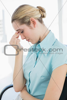 Tired businesswoman sitting on her swivel chair with eyes closed