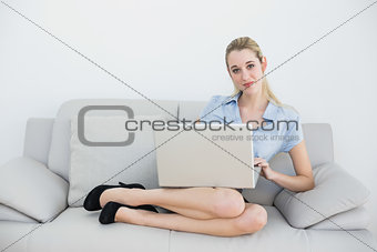 Attractive blonde businesswoman sitting on couch