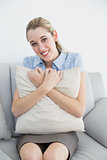 Cute chic businesswoman holding a pillow sitting on couch