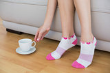 Young slender woman wearing pink socks sitting on couch