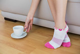 Slender woman wearing pink socks reaching for a cup