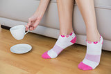 Young woman wearing pink socks holding a cup