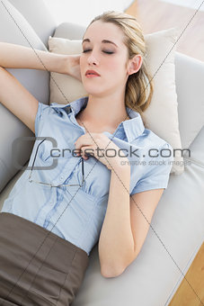 Beautiful calm businesswoman sleeping lying on her couch